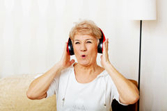 Femme supérieure heureuse utilisant les écouteurs rouges Photographie stock