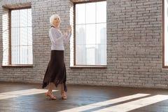Femme supérieure inspirée tangoing à la leçon de danse photo libre de droits