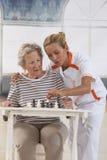 Femme supérieure jouant avec l'infirmière dans la retraite Photos stock