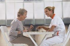 Femme supérieure jouant avec l'infirmière dans la retraite Photo stock
