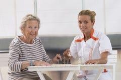 Femme supérieure jouant avec l'infirmière dans la retraite Images stock