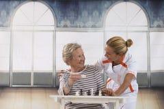 Femme supérieure jouant avec l'infirmière dans la retraite Images libres de droits