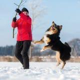 Femme supérieure jouant avec le chien dans la neige Photo stock