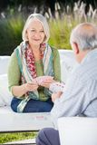 Femme supérieure jouant des cartes avec l'homme Photos libres de droits