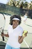 Femme supérieure jouant le tennis devant le tribunal Images stock