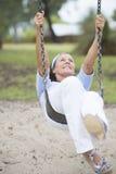Femme supérieure joyeuse sur la retraite d'active d'oscillation Photographie stock