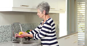 Femme supérieure lavant quelques légumes banque de vidéos