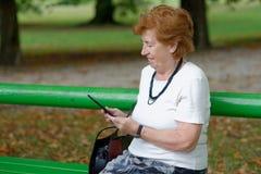 Femme supérieure lisant le lecteur d'EBook photos libres de droits