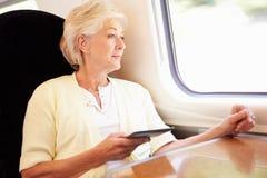 Femme supérieure lisant le livre d'E sur le voyage en train images libres de droits