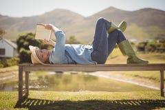 Femme supérieure lisant un livre tout en se trouvant sur le banc en parc Photographie stock