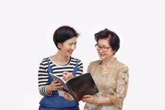 Femme supérieure lisant un magazine avec sa fille Photos libres de droits