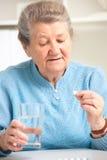 Femme supérieure lui prenant la médecine Photos stock