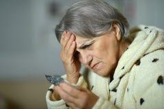 Femme supérieure malade avec des pilules Photographie stock libre de droits