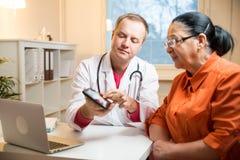 Femme supérieure malade ayant un rendez-vous de docteur image libre de droits