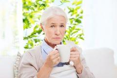 Femme supérieure malade buvant du thé chaud à la maison photographie stock