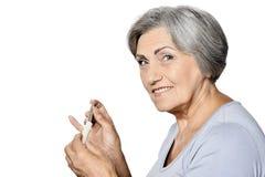 Femme supérieure malade prenant des pilules d'isolement Photographie stock