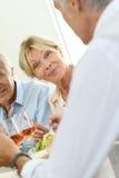Femme supérieure mangeant avec des amis Image stock