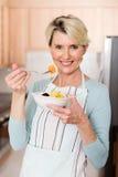 Femme supérieure mangeant de la salade de fruits photos libres de droits