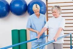 Femme supérieure marchant avec des barres parallèles avec le thérapeute Photo stock