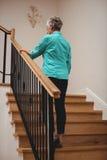 Femme supérieure marchant vers le haut des escaliers photos libres de droits