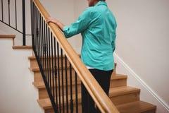 Femme supérieure marchant vers le haut des escaliers images stock