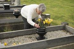 Femme supérieure mettant des fleurs sur une tombe Images libres de droits