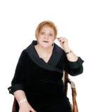 Femme supérieure mettant la prothèse auditive dessus Image stock