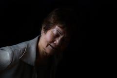 Femme supérieure montrant des douleurs de dos sur le fond noir Photos libres de droits