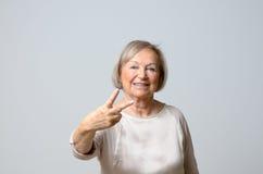 Femme supérieure montrant des signes de V Photo stock
