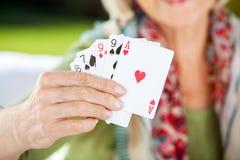 Femme supérieure montrant jouant des cartes Photos libres de droits