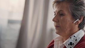 Femme supérieure musique se repose et de écoute par de nouveaux écouteurs sans fil modernes clips vidéos