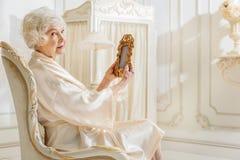 Femme supérieure observant la vieille photo de sa jeunesse Photographie stock libre de droits