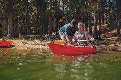 Femme supérieure obtenant des leçons kayaking d'un homme Photographie stock libre de droits