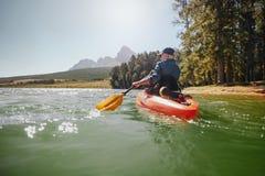 Femme supérieure obtenant des leçons kayaking d'un homme Photographie stock