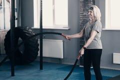 Femme supérieure optimiste s'exerçant avec des cordes de bataille Images libres de droits