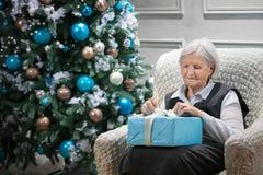 Femme supérieure ouvrant un paquet avec un cadeau Photos stock