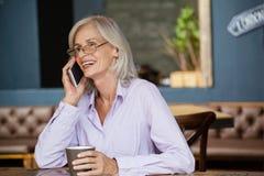 Femme supérieure parlant au téléphone intelligent tout en tenant la tasse au café Photo stock