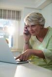 Femme supérieure parlant au téléphone portable tout en à l'aide de l'ordinateur portable Image stock