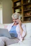 Femme supérieure parlant au téléphone portable tout en à l'aide de l'ordinateur portable dans le salon Photos libres de droits