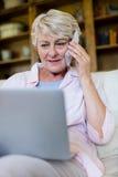 Femme supérieure parlant au téléphone portable tout en à l'aide de l'ordinateur portable dans le salon Image stock