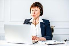 Femme supérieure parlant avec le casque au bureau Photos libres de droits