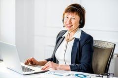 Femme supérieure parlant avec le casque au bureau Photo libre de droits