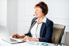 Femme supérieure parlant avec le casque au bureau Image libre de droits