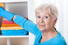 Femme supérieure pendant les travaux du ménage images stock