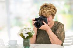 Femme supérieure photographiant des fleurs photos libres de droits