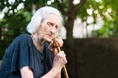 Femme supérieure pleurant avec une canne de marche image stock