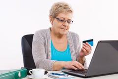 Femme supérieure pluse âgé avec la carte de crédit et ordinateur portable payant au-dessus de l'Internet des factures de service  Photos stock