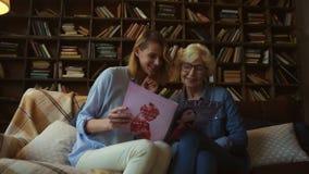 Femme supérieure positive et sa fille lisant une revue de mode banque de vidéos