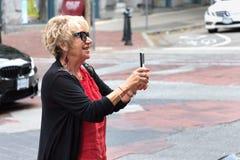 Femme supérieure prenant des photos avec son mobile Photo stock