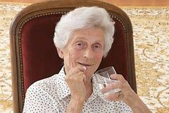 Femme supérieure prenant des pilules à la maison dans le salon Photos stock